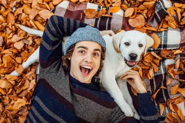 Atrakcyjny mężczyzna w szarej czapce leżącej na kocu ze swoim labradorem.