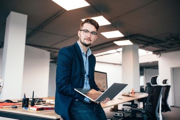 Atrakcyjny mężczyzna w szklance siedzi w pobliżu miejsca pracy w biurze. nosi niebieską koszulę, ciemną kurtkę. trzyma laptopa i patrzy w kamerę.