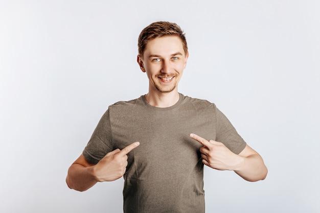 Atrakcyjny mężczyzna wskazuje na siebie obiema rękami. przystojny facet proponuje i się uśmiecha.