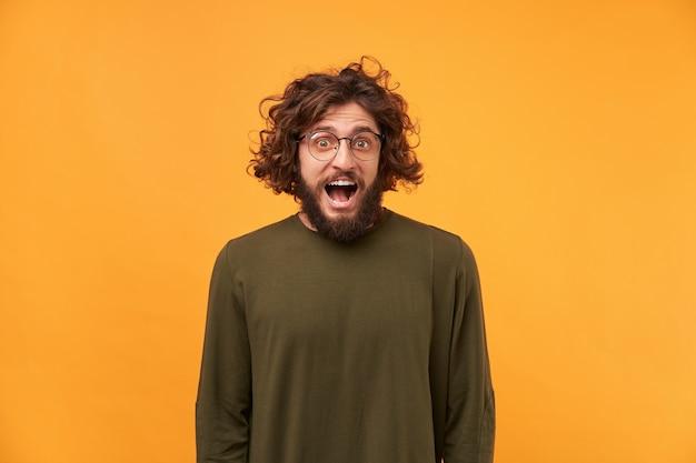 Atrakcyjny mężczyzna wygląda szczęśliwie radośnie, usta szeroko otwarte