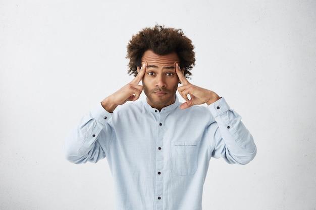 Atrakcyjny mężczyzna z krzaczastą fryzurą i zamyślonym spojrzeniem próbuje się skoncentrować