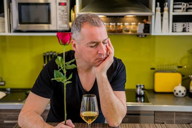 Atrakcyjny mężczyzna z kwiatami w ręku czeka. przemyślany mężczyzna w kuchni czeka na kobietę