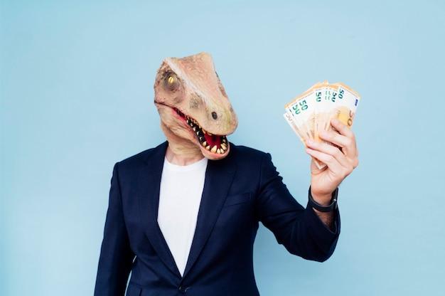 Atrakcyjny mężczyzna z maską dinozaura trzymający swoje pieniądze