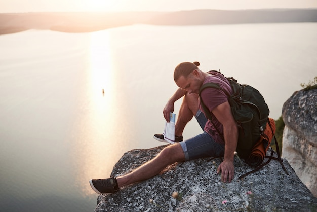 Atrakcyjny mężczyzna z widokiem na krajobraz gór nad powierzchnią wody.