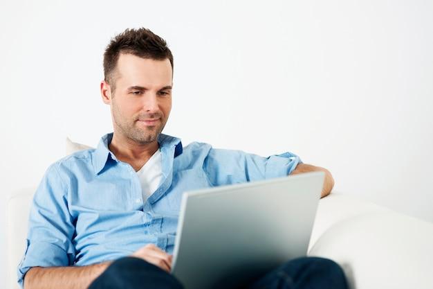Atrakcyjny mężczyzna za pomocą laptopa na kanapie