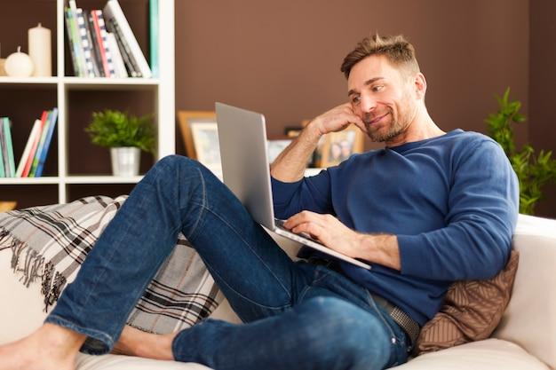 Atrakcyjny mężczyzna za pomocą laptopa w domu