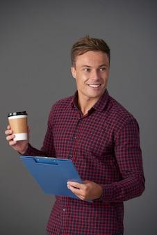 Atrakcyjny mężczyzna ze schowkiem i kawą