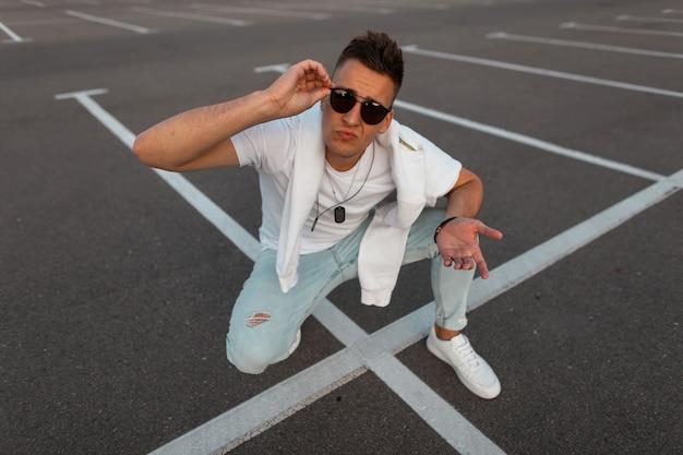 Atrakcyjny miejski młody człowiek w okularach przeciwsłonecznych w modnych ubraniach w modnych białych trampkach pozuje na asfalcie. przystojny miejski facet siedzieć na parkingu w mieście. stylowa młodzieżowa letnia odzież męska.