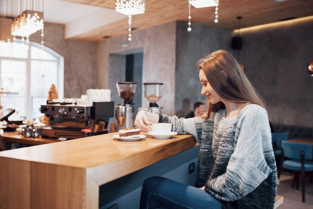 Atrakcyjny młodej kobiety siedzieć wewnątrz w miejskiej kawiarni. styl życia cafe city. przypadkowy portret nastolatek dziewczyna