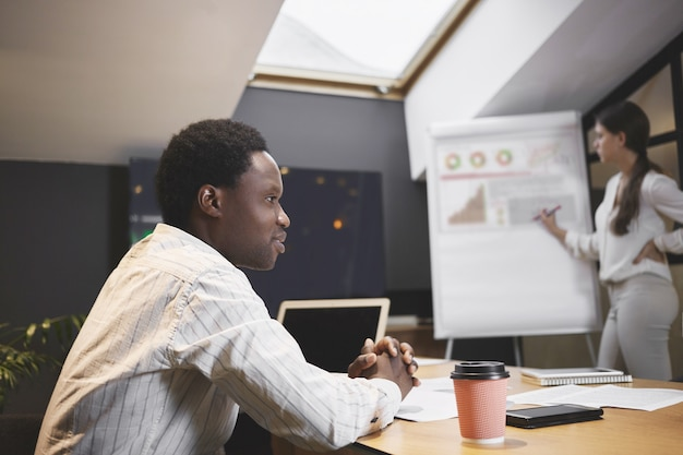 Atrakcyjny młody afrykański ceo siedzi w sali konferencyjnej podczas spotkania opracowującego strategię