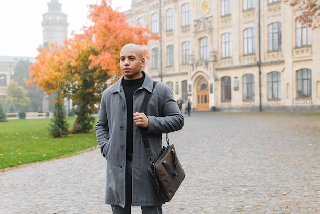 Atrakcyjny młody afrykański mężczyzna ubrany w jesienny płaszcz, chodzący na zewnątrz po ulicy miasta