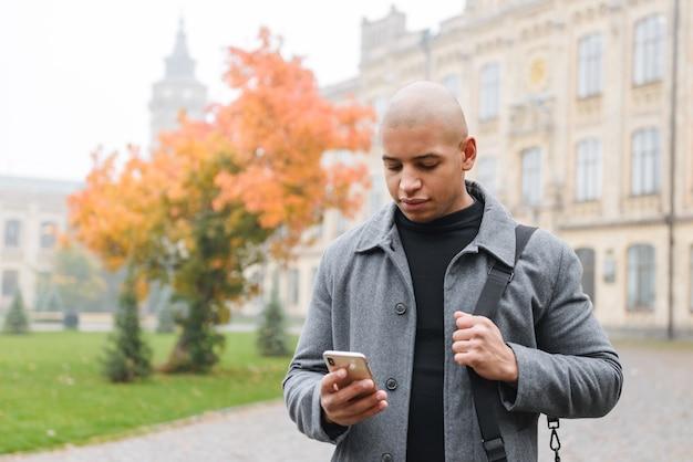 Atrakcyjny młody afrykański mężczyzna ubrany w jesienny płaszcz, spacerujący na świeżym powietrzu po ulicy miasta, przy użyciu telefonu komórkowego