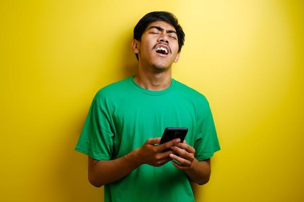Atrakcyjny młody azjatycki mężczyzna czytający sms-y na czacie na swoim telefonie, złe wieści, smutny płacz wyraz na żółtym tle