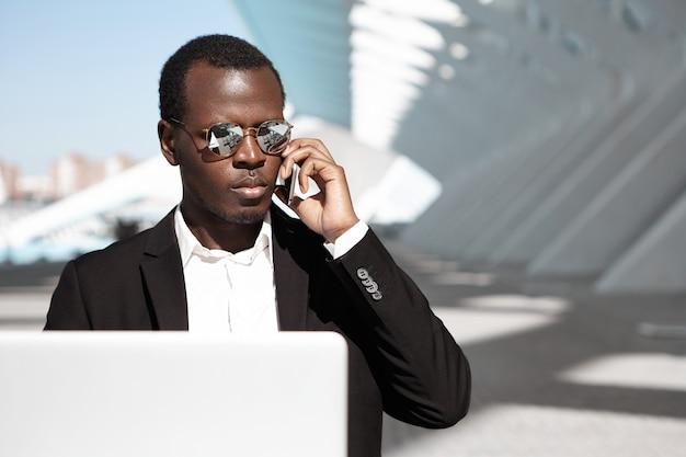 Atrakcyjny młody biznesmen afroamerykański w stylowych okularach przeciwsłonecznych i formalnym stroju siedzi w miejskiej kawiarni przed laptopem, rozmawiając telefonicznie z partnerami, czekając na kawę
