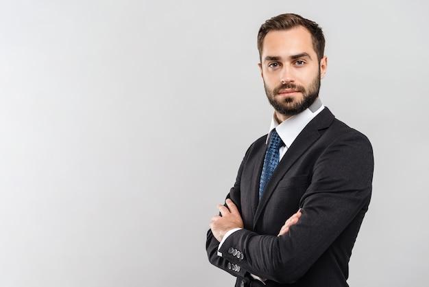 Atrakcyjny młody biznesmen ubrany w garnitur stojący na białym tle nad szarą ścianą, z założonymi rękoma