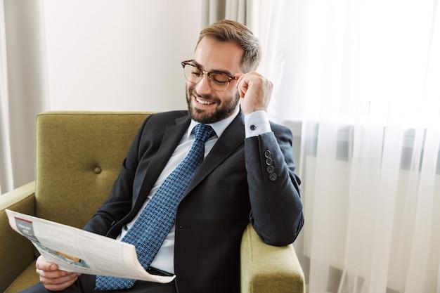 Atrakcyjny młody biznesmen w garniturze siedzi na krześle w pokoju hotelowym i czyta gazetę