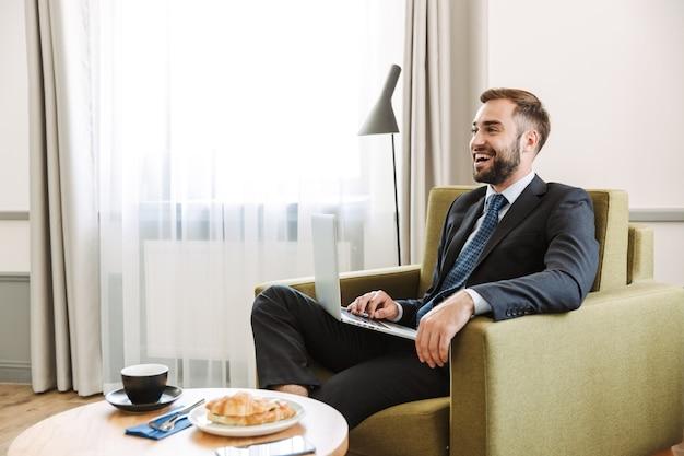 Atrakcyjny młody biznesmen w garniturze siedzi na krześle w pokoju hotelowym, pracując na laptopie podczas śniadania