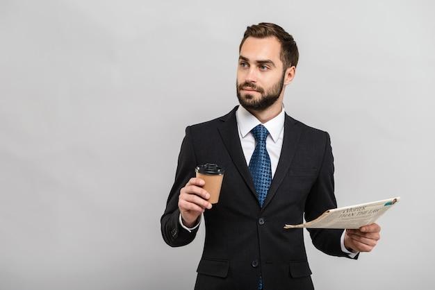Atrakcyjny młody biznesmen w garniturze stojący na białym tle nad szarą ścianą, czytający gazetę podczas picia kawy na wynos