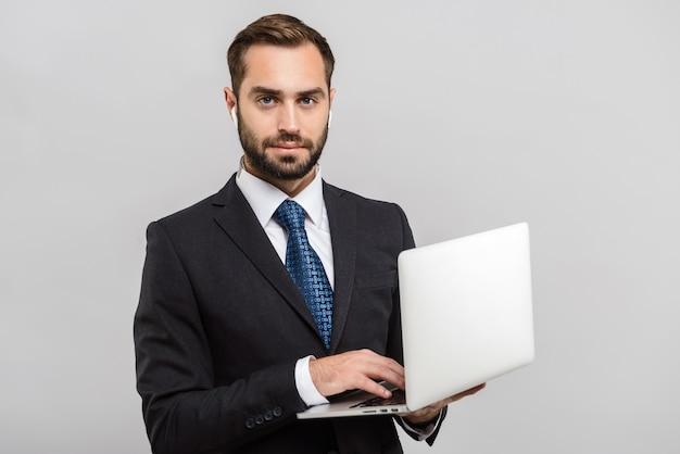 Atrakcyjny młody biznesmen w garniturze stojący na białym tle nad szarą ścianą, korzystający z laptopa