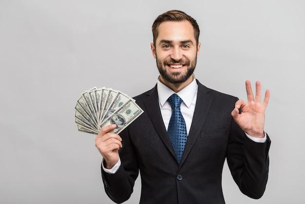 Atrakcyjny młody biznesmen w garniturze stojący na białym tle nad szarą ścianą, pokazujący banknoty pieniędzy, ok