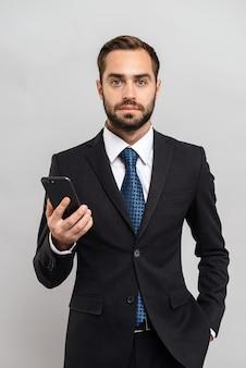 Atrakcyjny młody biznesmen w garniturze stojący na białym tle nad szarą ścianą, trzymający telefon komórkowy