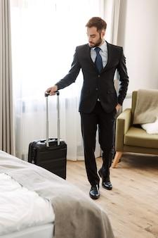 Atrakcyjny młody biznesmen w garniturze stojący w pokoju hotelowym, niosący walizkę, właśnie przyjechał