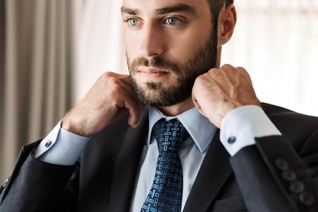 Atrakcyjny młody biznesmen w garniturze stojący w pokoju hotelowym, ubierający się