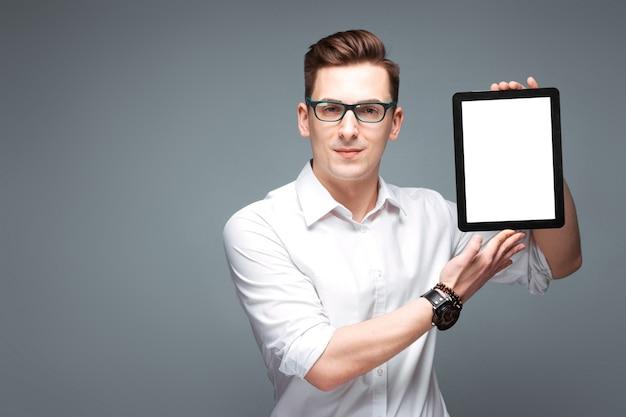 Atrakcyjny młody biznesmen w kosztowny zegarek, czarne okulary i białą koszulę trzymać pustą tabletkę