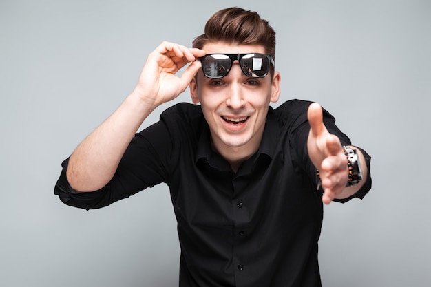 Atrakcyjny młody biznesmen w kosztownym zegarku, okularach przeciwsłonecznych i czarnej koszuli