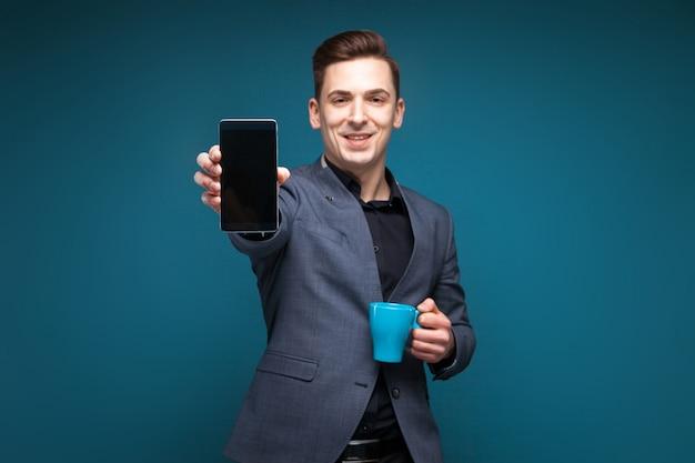 Atrakcyjny młody biznesmen w szarej kurtce i czarnej koszula trzyma błękitną filiżankę i pokazuje telefon