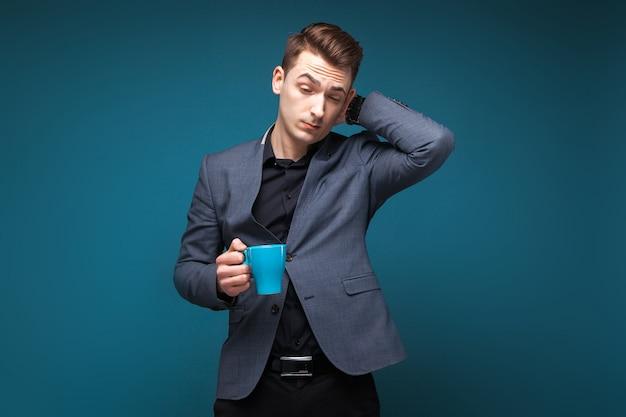Atrakcyjny młody biznesmen w szarej kurtce i czarnej koszuli trzymać niebieski kubek