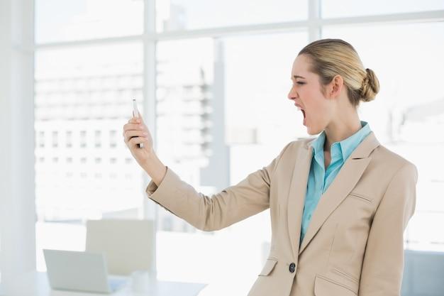 Atrakcyjny młody bizneswoman patrzeje szokujący przy jej smartphone