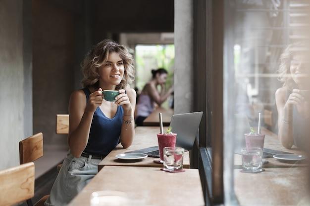 Atrakcyjny młody blond marzycielski cyfrowy nomad siedzi pije kawę kawiarnia miejska przestrzeń coworkingowa wygląda za oknem uśmiechnięty marzycielski zamyślony cieszy się przerwą pracując nad projektem freelancer. koncepcja gospodarki gig.