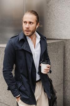 Atrakcyjny młody blond włosy mężczyzna w wizytowym stroju rozmawia przez słuchawki, trzymając filiżankę kawy na wynos stojąc na zewnątrz na ulicy miasta
