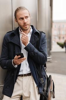 Atrakcyjny młody blondyn w stroju wizytowym rozmawia przez słuchawki, trzymając telefon komórkowy, stojąc na zewnątrz na ulicy miasta