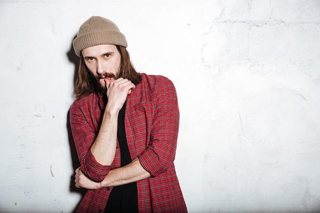 Atrakcyjny młody brodaty hipster mężczyzna w kapeluszu ubrany w koszulę w klatce odizolowanej nad ścianą, patrząc na przód