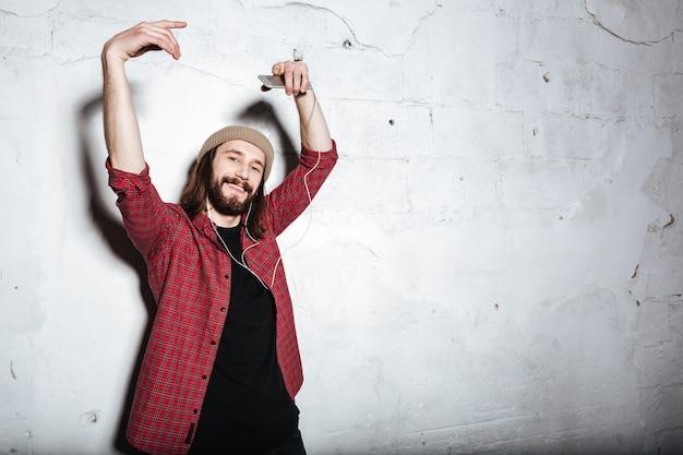 Atrakcyjny młody brodaty hipster mężczyzna w kapeluszu ubrany w koszulę w klatce odizolowanej nad ścianą, patrząc z przodu podczas słuchania muzyki przez słuchawki