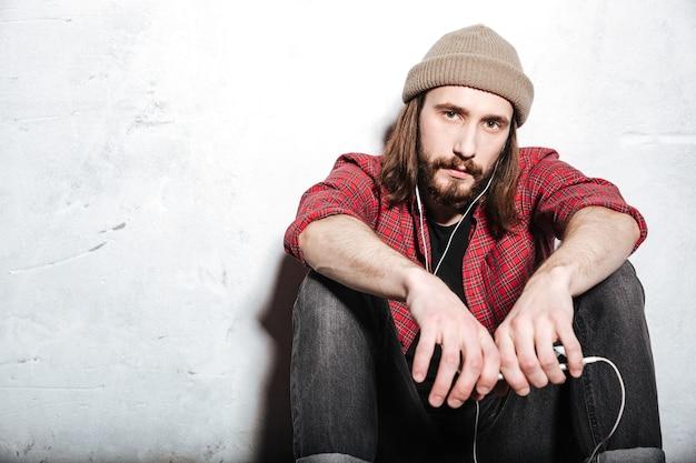 Atrakcyjny młody brodaty hipster mężczyzna w kapeluszu ubrany w koszulę w klatce, siedzący na podłodze odizolowanej nad ścianą podczas słuchania muzyki przez słuchawki