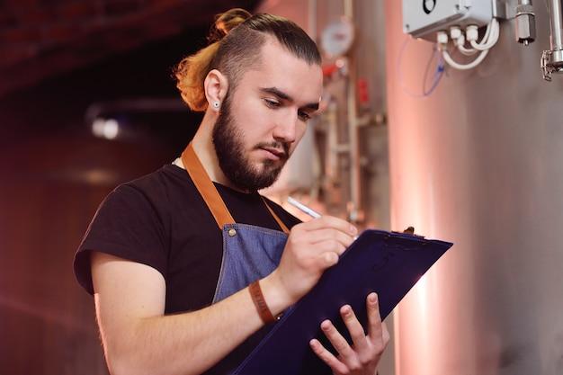 Atrakcyjny młody browar z brodą bada sprzęt do warzenia i zapisuje wyniki na papierze.
