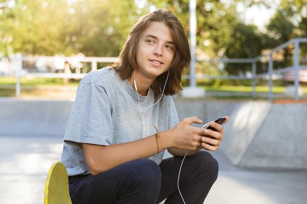 Atrakcyjny młody chłopak spędza czas w skate parku, słuchając muzyki przez słuchawki