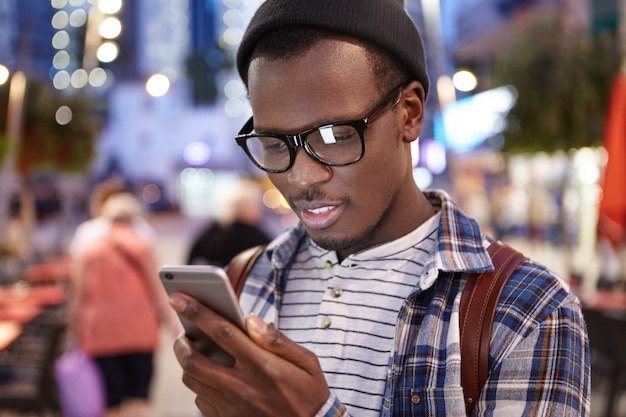 Atrakcyjny, młody, ciemnoskóry europejski autostopowicz z plecakiem, w modnych okularach i kapeluszu, badający trasy i lokalizacje na mapie online na swoim smartfonie, stojący w środku obcego miasta