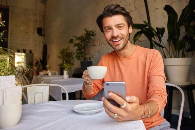 Atrakcyjny młody ciemnowłosy mężczyzna w swetrze pozuje nad wnętrzem kawiarni, trzyma srartphone w dłoni i patrzy wesoło, popijając kawę