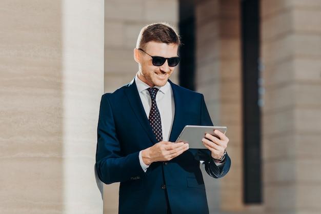Atrakcyjny młody człowiek czyta ważne informacje na komputerze typu tablet