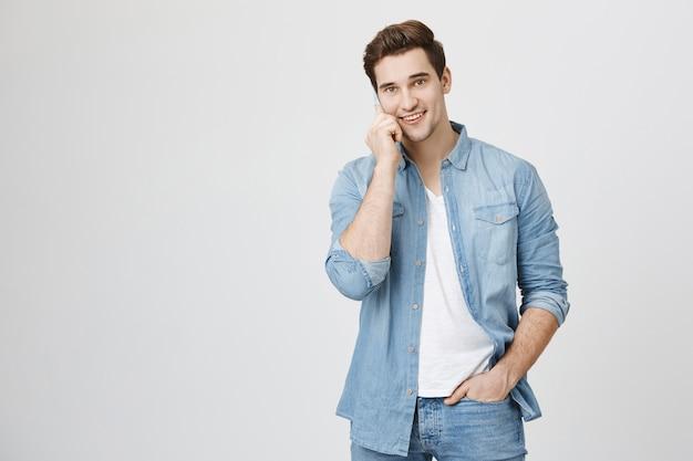 Atrakcyjny młody człowiek ma rozmowę telefoniczną, rozmawia i uśmiecha się