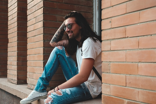 Atrakcyjny młody człowiek nosi okulary przeciwsłoneczne