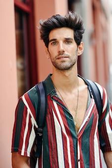 Atrakcyjny młody człowiek o ciemnych włosach i nowoczesnej fryzurze na sobie ubranie na zewnątrz