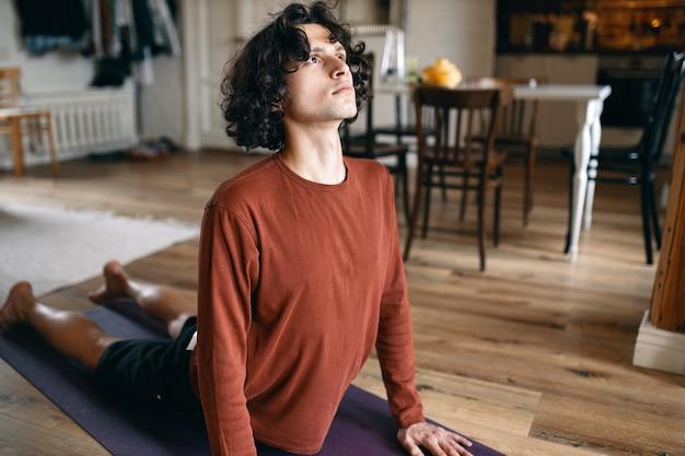 Atrakcyjny młody człowiek rasy kaukaskiej w ubranie robi sekwencję jogi na powitanie słońca, rozciągając klatkę piersiową w skierowanym w górę psem lub urdhva mukha svanasana.