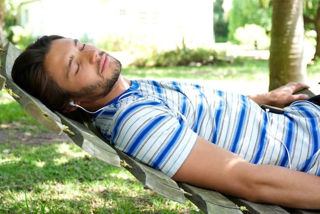 Atrakcyjny młody człowiek relaksuje na hamaku z hełmofonami