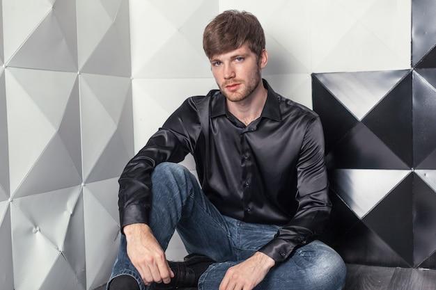 Atrakcyjny młody człowiek siedzi na podłodze