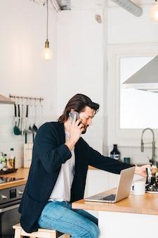 Atrakcyjny młody człowiek siedzi w kuchni rozmawia przez telefon komórkowy
